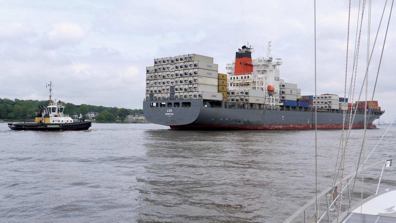 Hinaaja jarruttaa konttilaivaa Hampurin satamassa