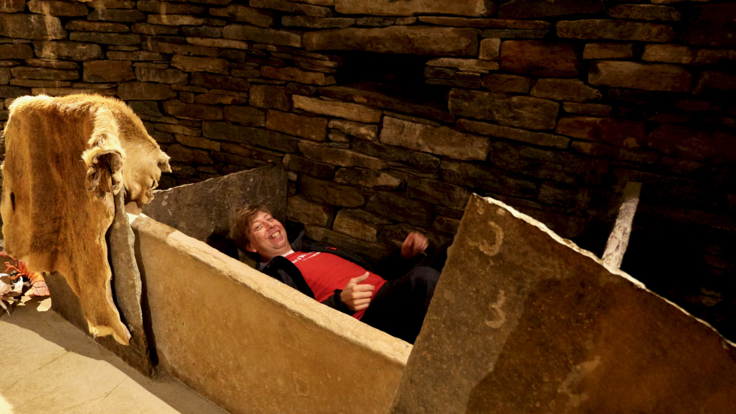 Andrus testing the stone bed in the replica house of Skara Brae