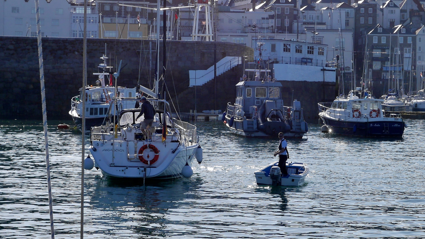 Harbour staff of St Peter Port welcoming a yacht in Guernsey