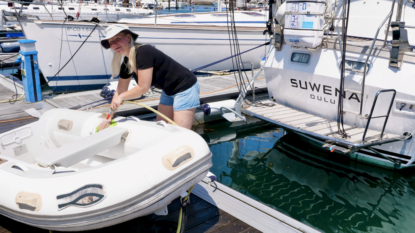 Eve washing a dinghy in Sada, Spain